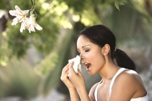 Woman sneezing under tree