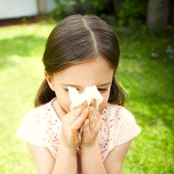 Young girl blowing her nose because of an allergy